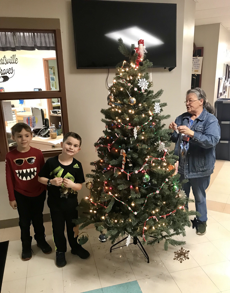 Our lead custodian Debbie Arnold and two 1st grade students decorating the Robertsville Christmas tree.