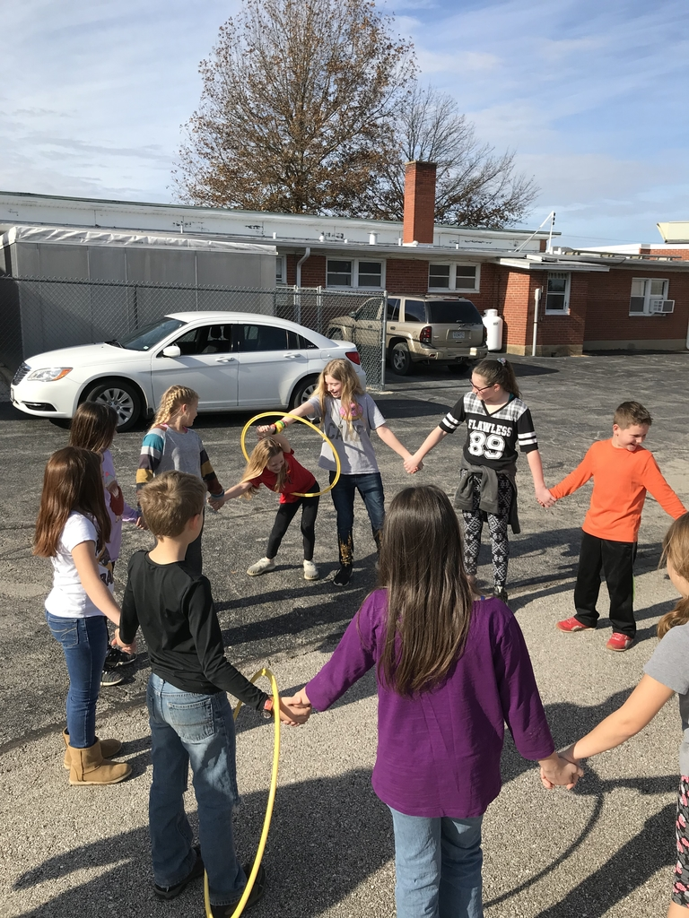 Ms. Rusin's 4th grade doing a team building activity. The hula hoops were going in different directions so students had to work together to move them around the circle with letting go.